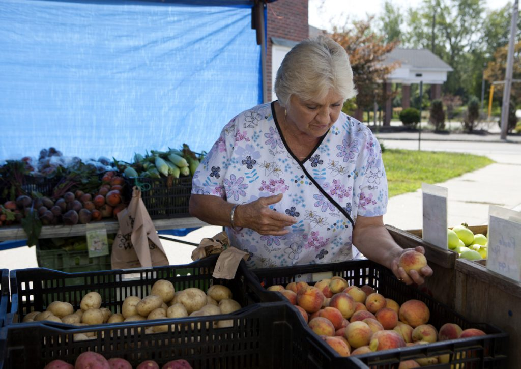 Ruth Knight, 73, of South Portland picks out produce Sunday at the farmers market in the city's Knightville neighborhood.