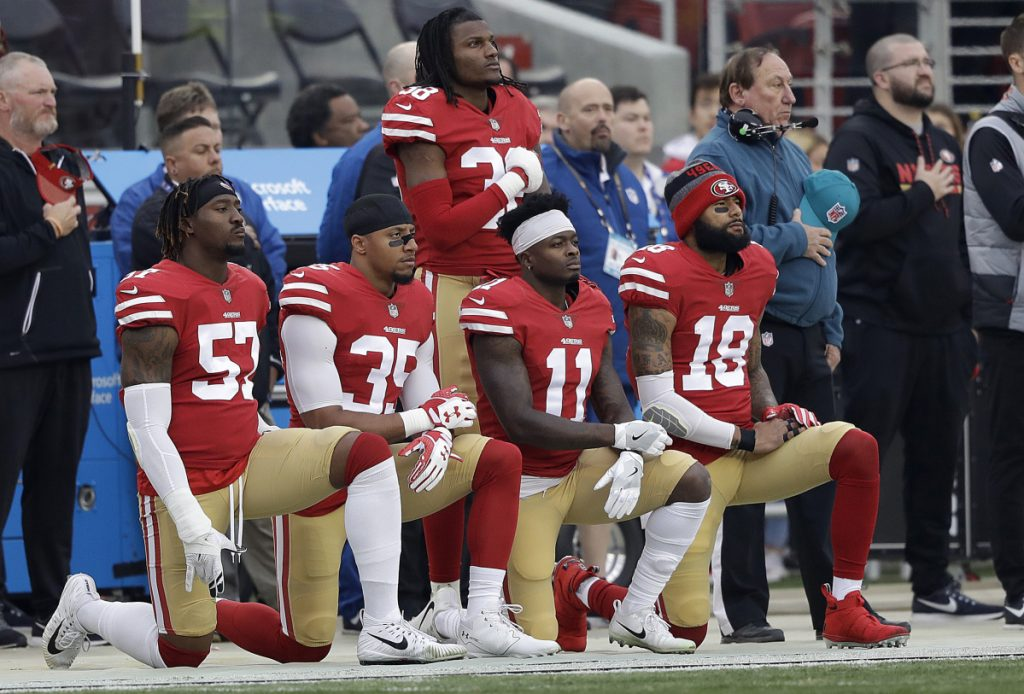 FILE - In this Dec. 24, 2017, file photo, San Francisco 49ers outside linebacker Eli Harold, from bottom left, kneels with safety Eric Reid, wide receiver Marquise Goodwin and wide receiver Louis Murphy during the national anthem before an NFL football game against the Jacksonville Jaguars in Santa Clara, Calif. With the unilateral policy banning players from any on-field protests during the anthem on hold as owners and players discuss the issue, no one can be sure what's ahead. (AP Photo/Marcio Jose Sanchez, File)