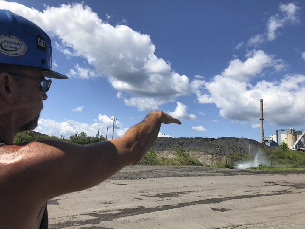 Brian Weekly, a contractor, points out the smokestack of a coal-fired power plant in Grant Town, W.Va. Weekly says coal foes are behind warnings of health risks from emissions.