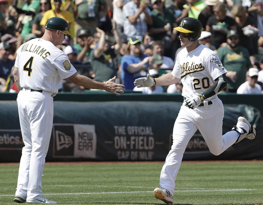 Mark Canha of the Athletics, right, is congratulated by third-base coach Matt Williams after hitting a solo home run against the Yankees during Oakland's 6-3 victory at home on Monday.