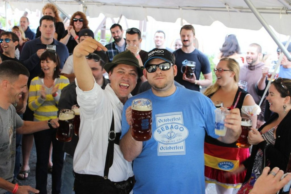 Kai Adams, left, vice president and co-founder of Sebago Brewing, congratulates last year's winner of the Oktoberfest stein-holding contest, Dave Snyder.