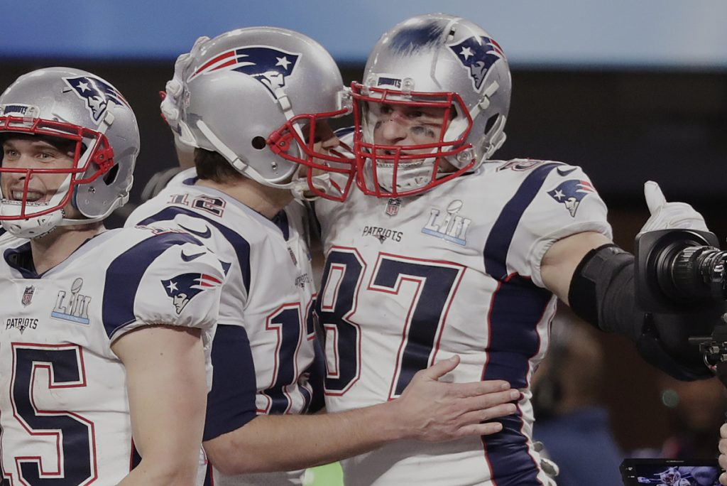 Quarterback Tom Brady has one of his top weapons, Rob Gronkowski, right, back and the tight end is happy after the Patriots added incentives to his contract.