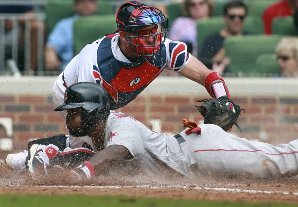 Boston's Brandon Phillips slides home safely to score past Atlanta Braves catcher Tyler Flowers during the eighth inning Wednesday in Atlanta. Phillips then hit the game-winning home run in the ninth inning as Boston won, 9-8.