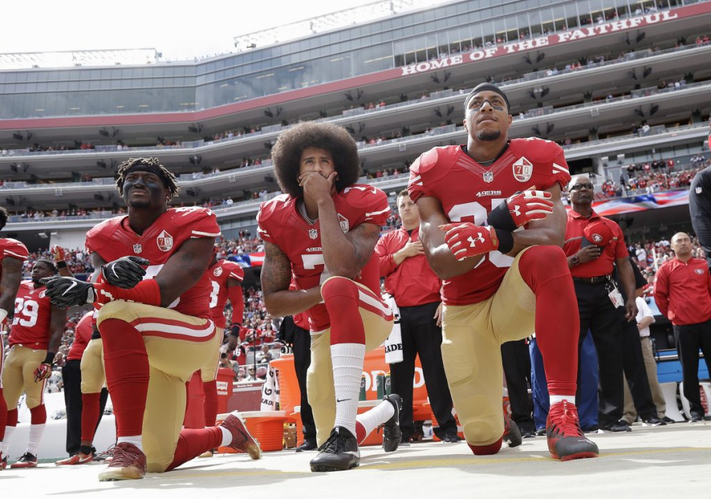 From left, San Francisco 49ers outside linebacker Eli Harold, then-quarterback Colin Kaepernick and safety Eric Reid kneel during the national anthem before a game against the Dallas Cowboys on Oct. 2, 2016. Most of the athletes who have participated in the ongoing protest have not only taken a knee but also donated money and time to solving problems in their own communities.
