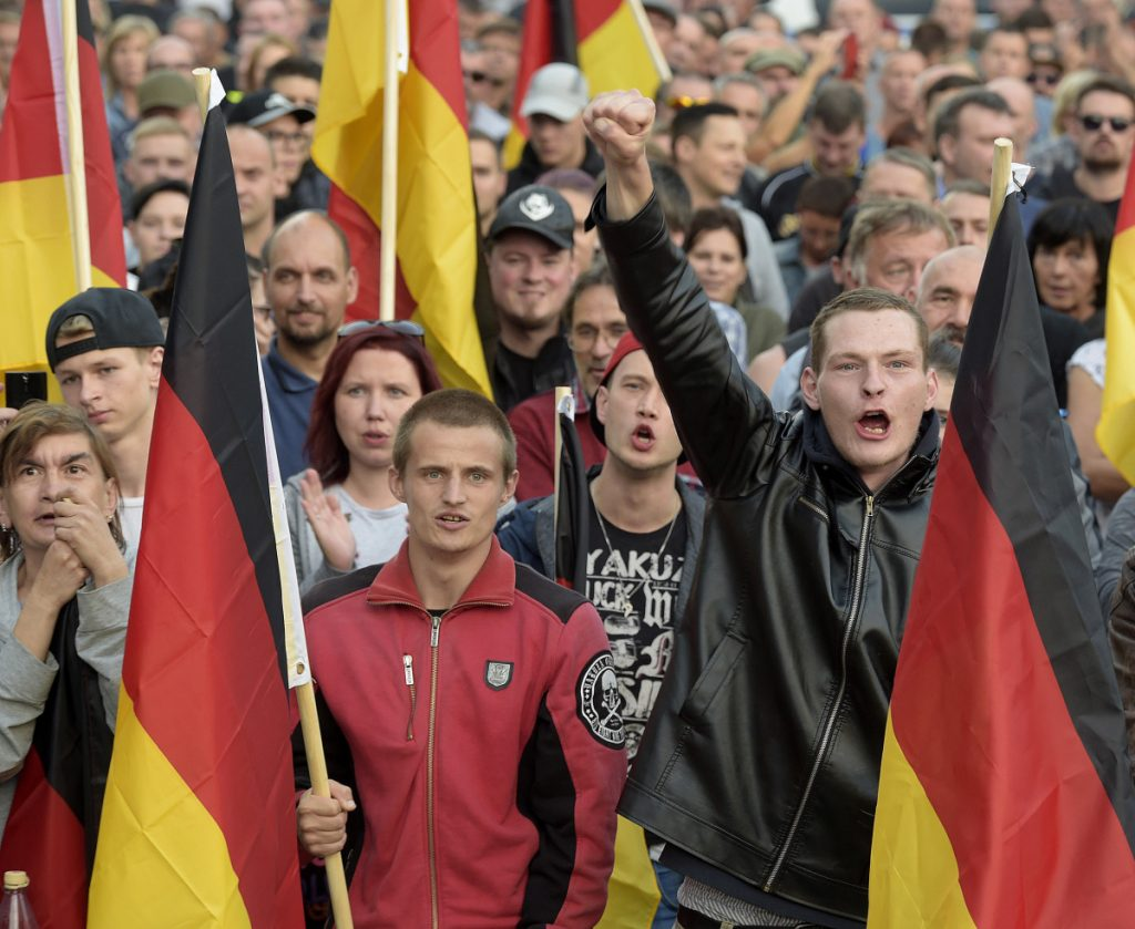 Far-right Germans march in Chemnitz on Friday. The far right is causing headaches for Chancellor Angela Merkel, who has welcomed immigrants.