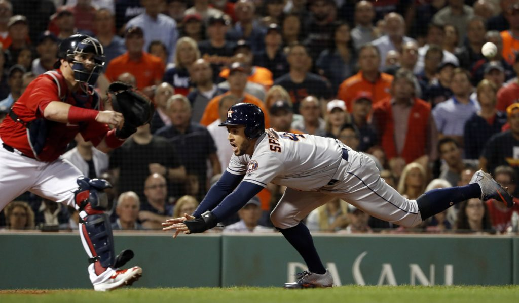 Houston's George Springer goes for a headfirst slide into home as Red Sox catcher Sandy Leon gets a late throw during the eighth inning Friday night at Fenway Park.