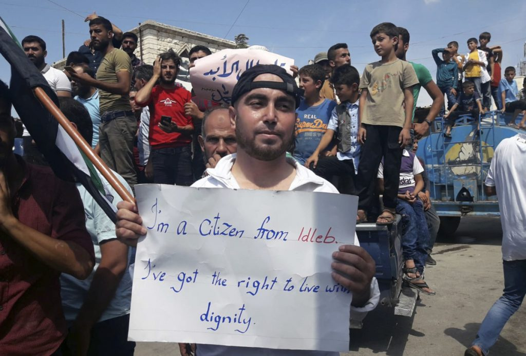 A protester holds a placard, in Harim, Syria, on Friday. The rallies were part of a day of protests against Syrian President Bashar Assad and his troops' imminent offensive against Idlib, the last bastion of rebels in Syria.