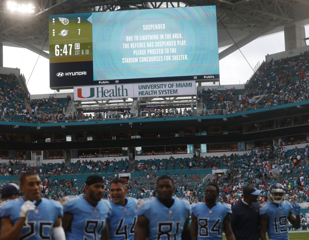 Tennessee Titans players leave the field after a second lightning delay was called during the second half of their game against the Dolphins on Sunday in Miami Gardens, Florida.