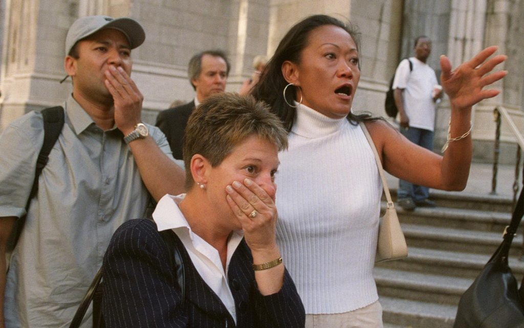 People in front of New York's St. Patrick's Cathedral react with horror as they look down Fifth Avenue toward the World Trade Center towers after planes crashed into their upper floors on Sept. 11, 2001.