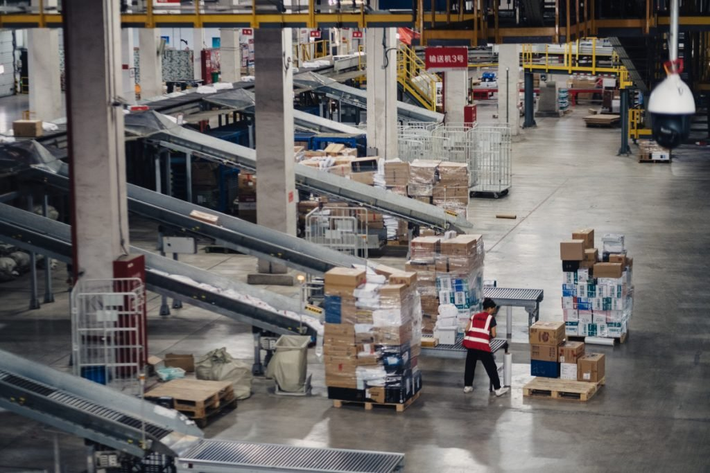 """A member of JD.com's staff works, nearly alone, in the company's sprawling warehouse near Shanghai. """"I don't get lonely,"""" says one of the four human workers staffing the place, """"because of the robots."""""""