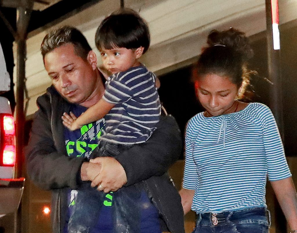 A Honduran man and his children proceed to a transport vehicle after being detained July 18 by Border Patrol agents in San Luis, Ariz.