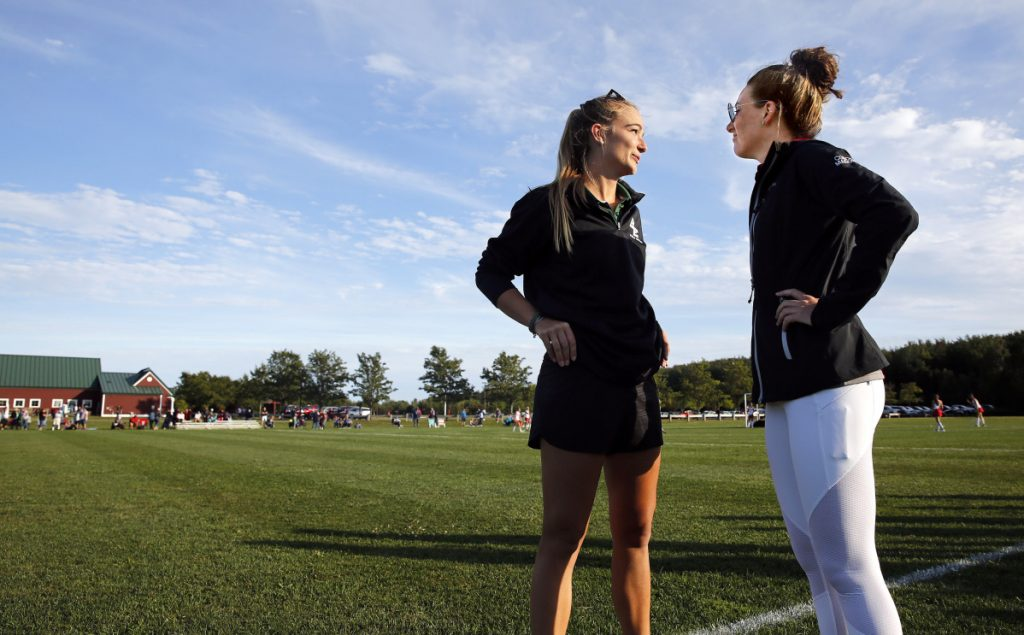 Field hockey coaches Vonde Saunders, left, of Bonny Eagle and Olivia Madore of South Portland chat after their teams played each other last Friday. A year ago, Saunders and Madore were senior teammates on the University of New England's field hockey team.