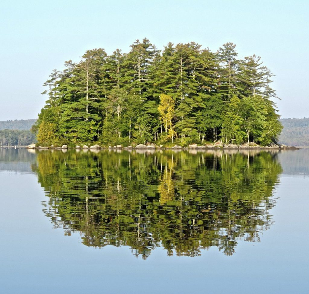 Round Island at Great Moose Lake in Hartland offers a perfect green circle mirrored in the calm water.