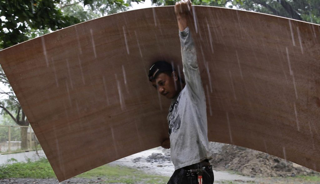 A worker uses a sheet of plywood to cover himself from the rain as Typhoon Mangkhut nears the northeastern Philippines on Friday.