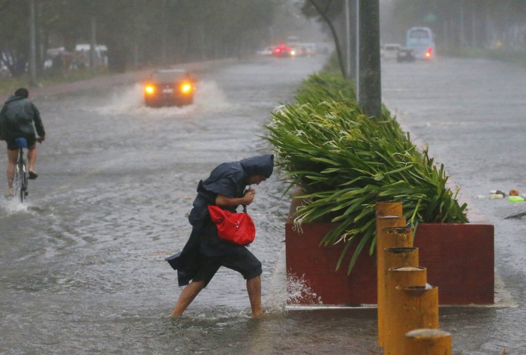 Commuters in Manila brave rain and strong winds from Typhoon Mangkhut, which barreled into the northeastern Philippines before dawn on Saturday.