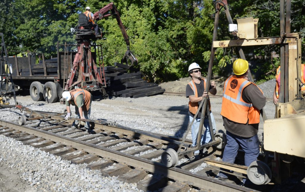 Crews work to replace rail ties along the Amtrak Downeaster line off Forest Avenue in Portland on Friday. The project is expected to be completed in October.