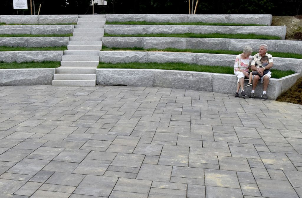 Donna and Leonard Dow and their grandson Owen rest on the steps of the granite amphitheater at the RiverWalk at Head of Falls in Waterville on Monday.