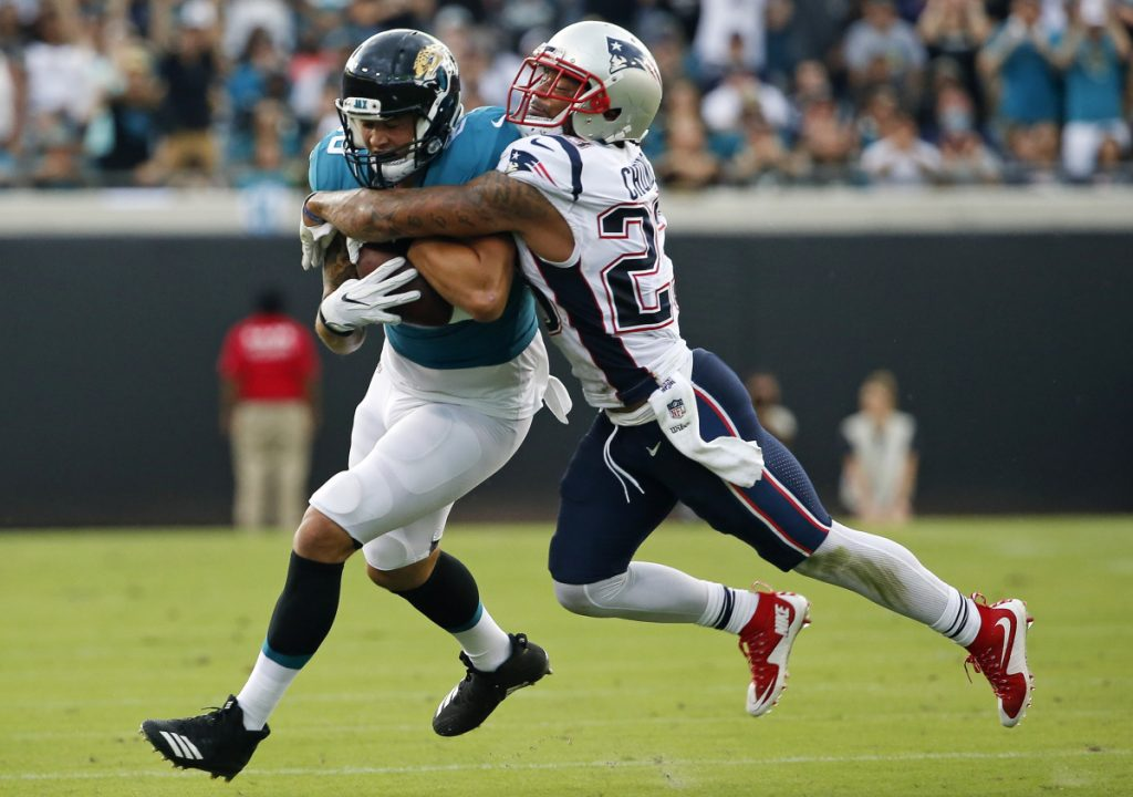 Safety Patrick Chung, right, tackles Jacksonville's James O'Shaughnessy on Sunday. Chung suffered an apparent head injury and was sent off the field by officials, but came back one play later. He did not play the second half.