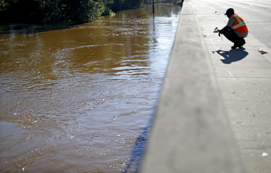 Maine Johnson with the city communications department in Fayetteville, N.C., takes photos of the Cape Fear River on Wednesday after its projected time of cresting.