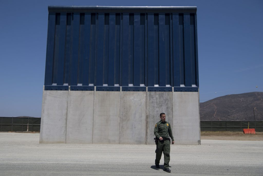 Border Patrol Public Affairs Officer Vincent Pirro looks at border wall prototypes that stand in the San Diego sector of the border wall in April.