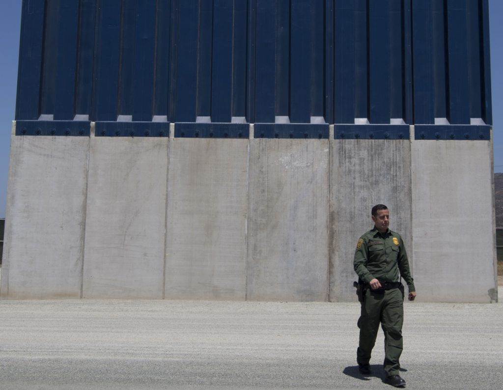 A Border Patrol official inspects border wall prototypes in the San Diego area last April.