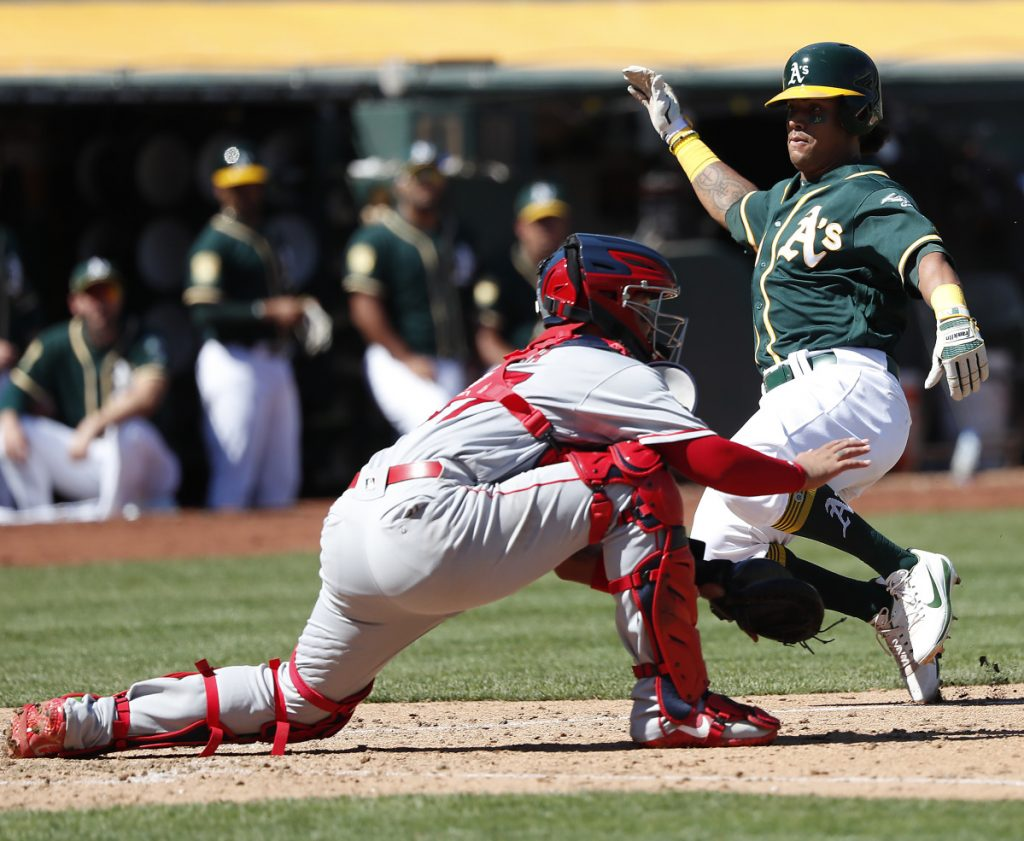 Oakland's Khris Davis slides past Angels catcher Francisco Arcia to score on a single by Stephen Piscotty in the fourth inning Thursday in Oakland, Calif. Later in the game, Arcia pitched the final two innings and allowed three runs as Oakland crushed Los Angeles, 21-3.