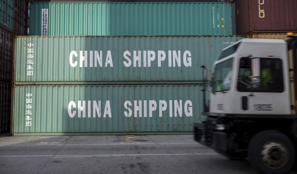 A truck passes a stack of 40-foot China shipping containers at the Port of Savannah in Georgia.