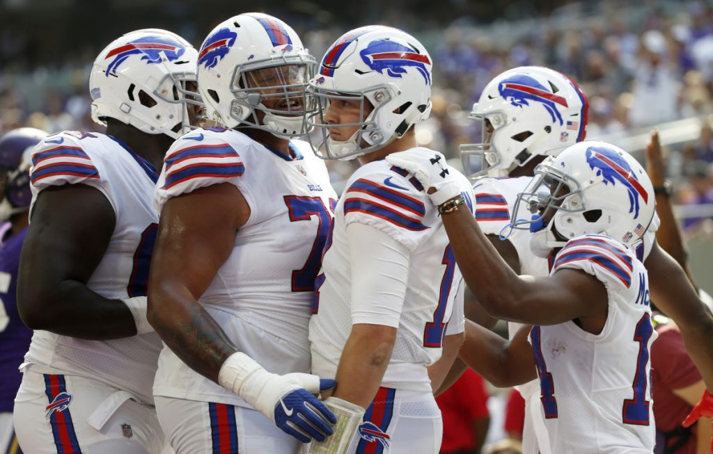Bills quarterback Josh Allen, center, celebrates with teammates after scoring on a 10-yard run Sunday against the Vikings. Allen ran for two TDs and passed for one in a 27-6 win.