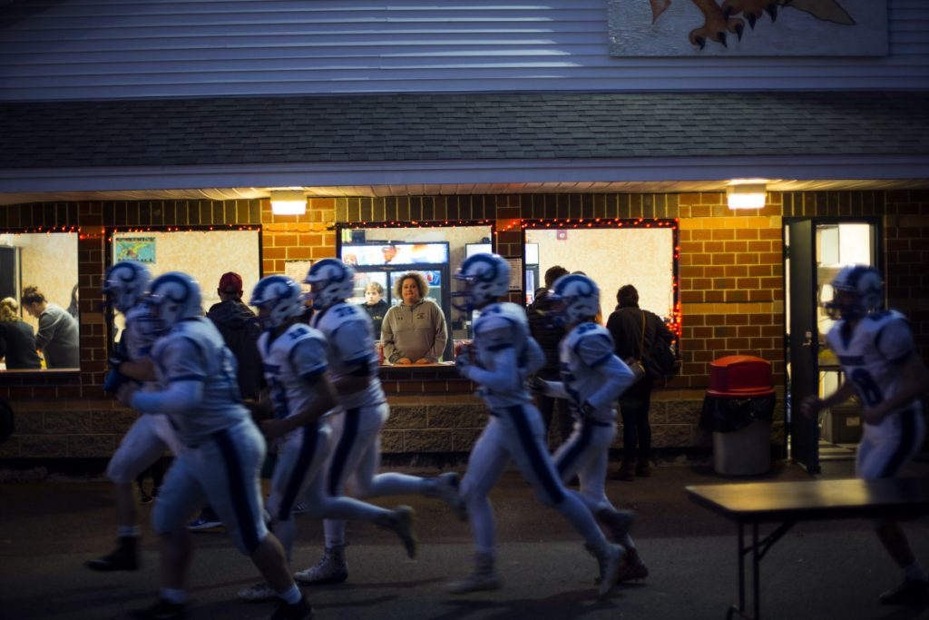 Volunteers work at the concession stand at Brunswick High School on Sept. 21, while visiting Kennebunk players run to the field.