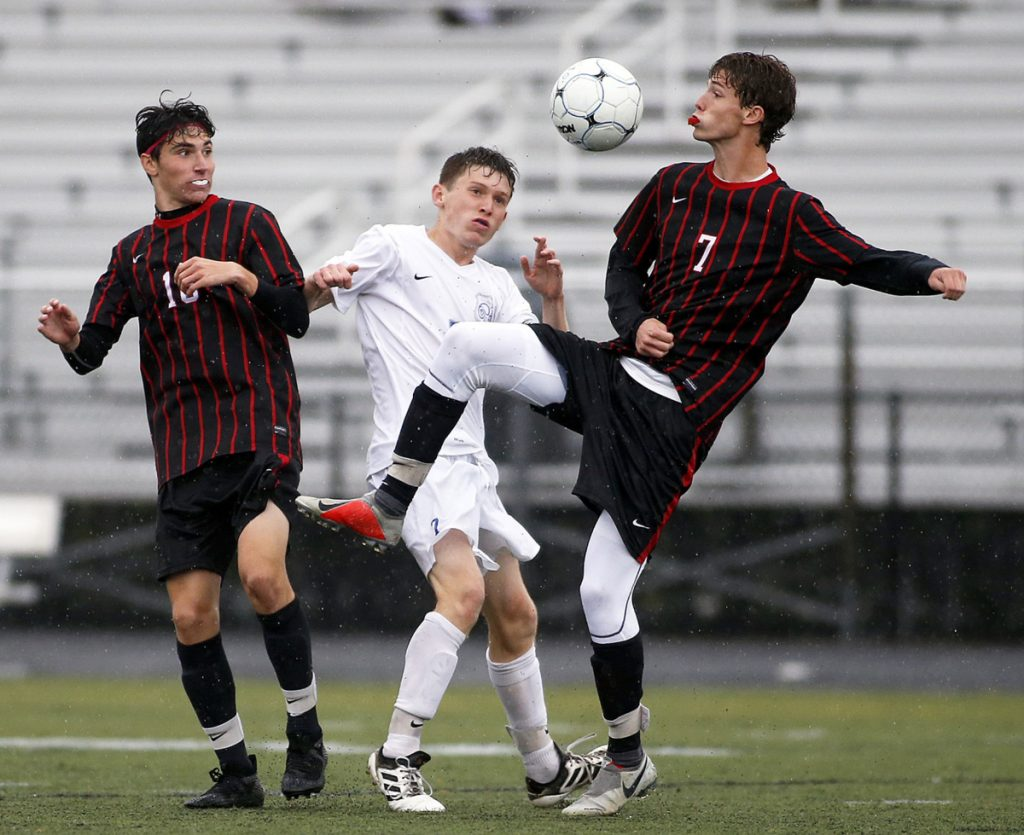 Scarborough's Matthew Ricker, left, and Liam Bridgham vie with Kennebunk's James Rogers for the ball in Tuesday's boys' soccer game at Scarborough. The Red Storm won 1-0 to move up to fourth in the Class A South Heal point standings.