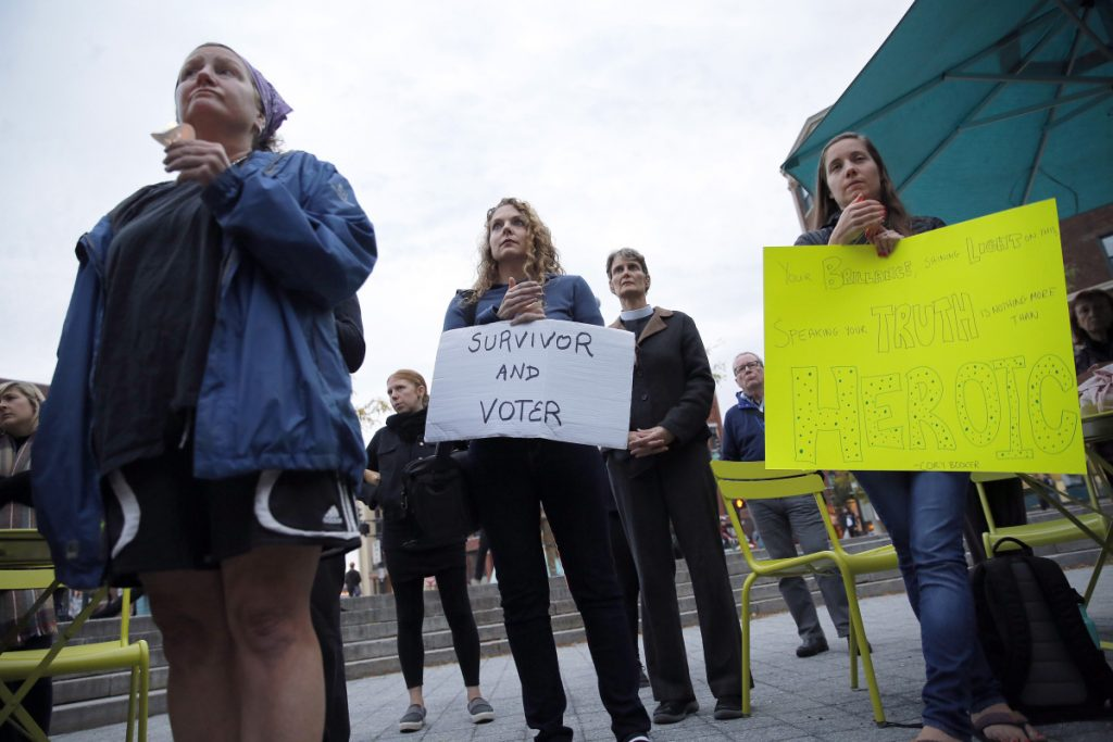 PORTLAND, ME - SEPTEMBER 27: Jennifer Porter, center, of Boston, Massachusetts, holds a sign during a candlelight vigil on Thursday in Congress Square Park. The vigil was held in solidarity with sexual assault survivors and inspired by Christine Blase Ford's decision to testify against Judge Brett Cavanaugh before the Senate Judiciary Committee. Porter said she had been sexually assaulted in high school and college. (Staff photo by Ben McCanna/Staff Photographer)