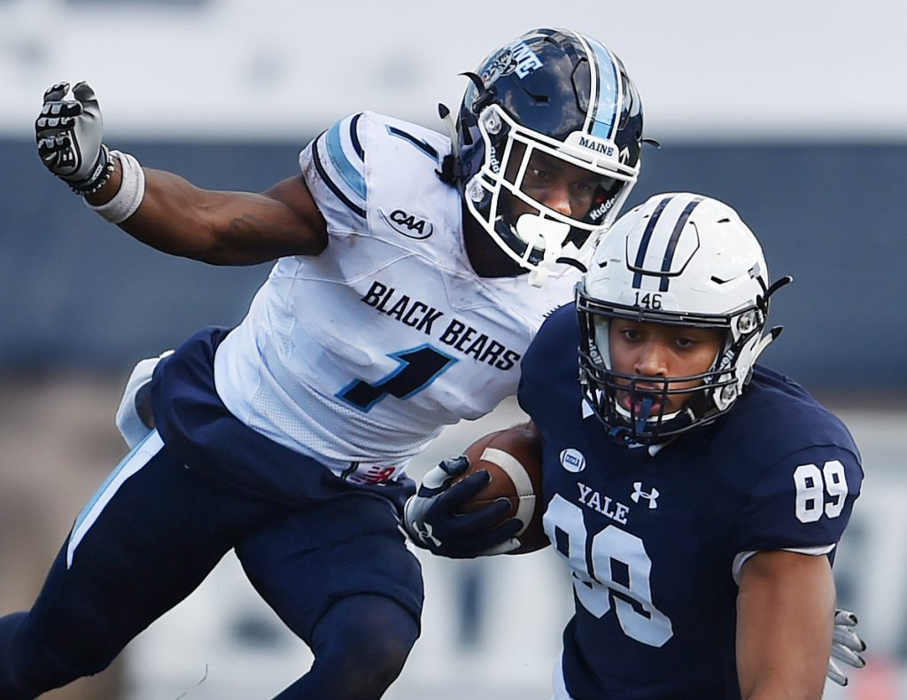 Manny Patterson of the University of Maine reaches for D. Major Roman of Yale during Saturday's game at the Yale Bowl in New Haven, Conn. Yale defeated Maine 35-14.