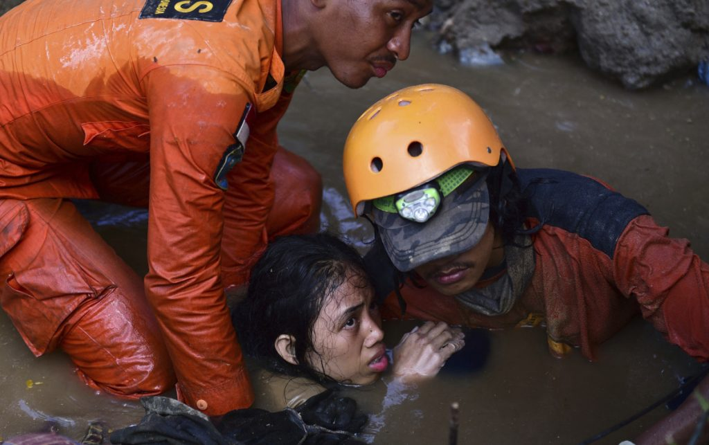 Rescuers try to help 15-year-old earthquake victim Nurul Istikharah from her damaged house following an earthquake and tsunami in Palu, central Sulawesi, Indonesia, on Sunday. Rescuers were scrambling to find victims trapped in collapsed buildings where voices could be heard.