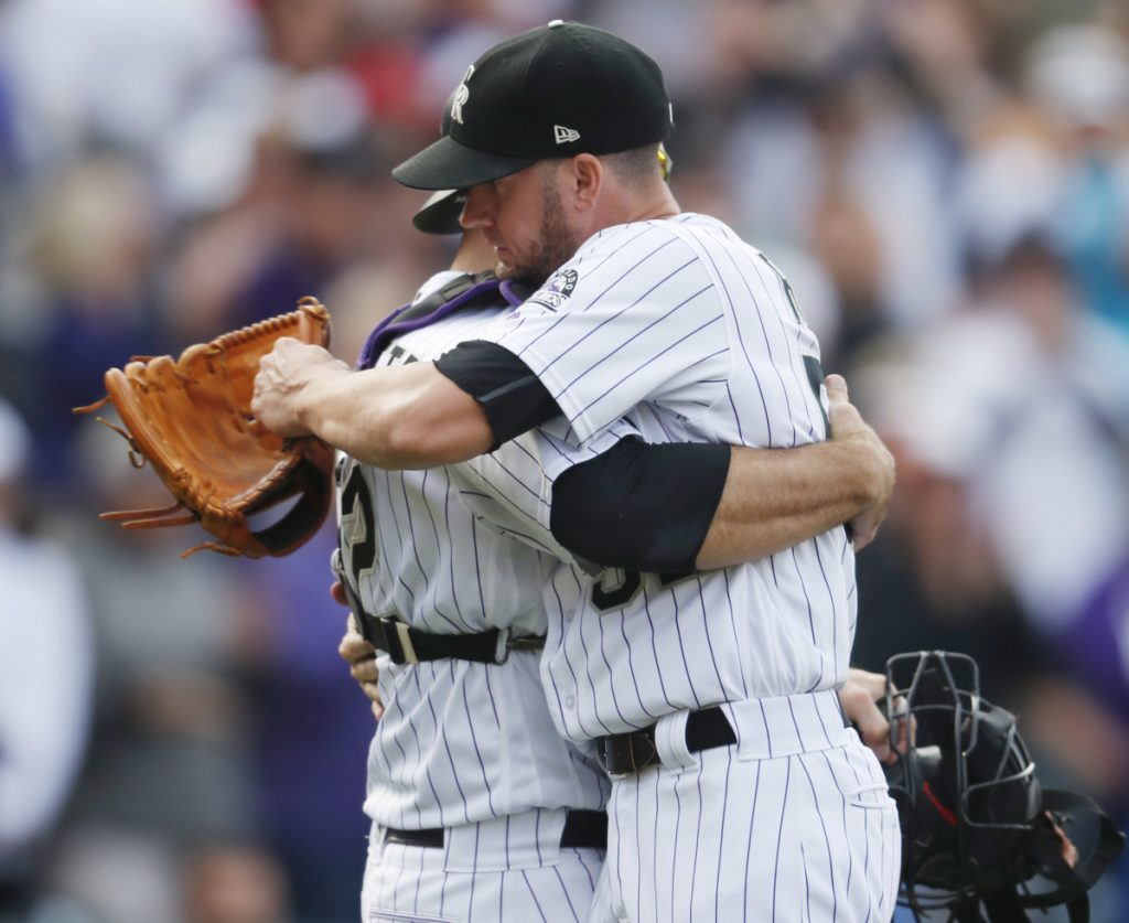 Rockies catcher Chris Iannetta, left, hugs reliever Chris Rusin after Colorado's 12-0 rout of the Nationals in Denver on Sunday put the Rockies in a playoff for the NL West crown.