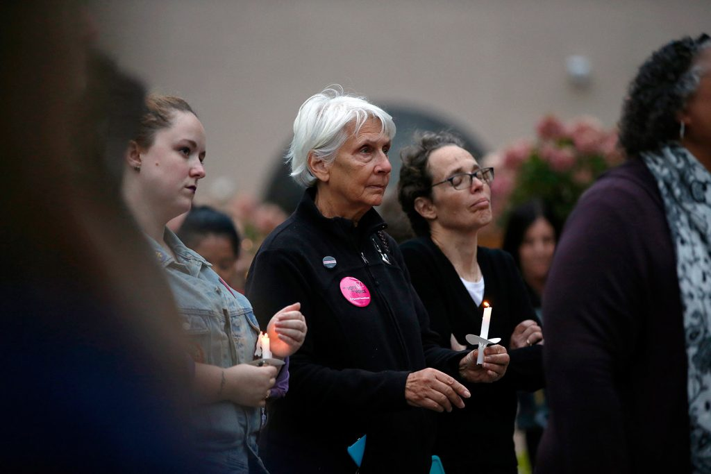 Susan Johnston, center left, of Cape Elizabeth and Claudia Sayre of Kennebunk listen to one of five speakers at a candlelight vigil Thursday in Portland's Congress Square Park. The vigil was held in solidarity with sexual assault survivors and inspired by Christine Blase Ford's decision to testify against Judge Brett Cavanaugh before the Senate Judiciary Committee.