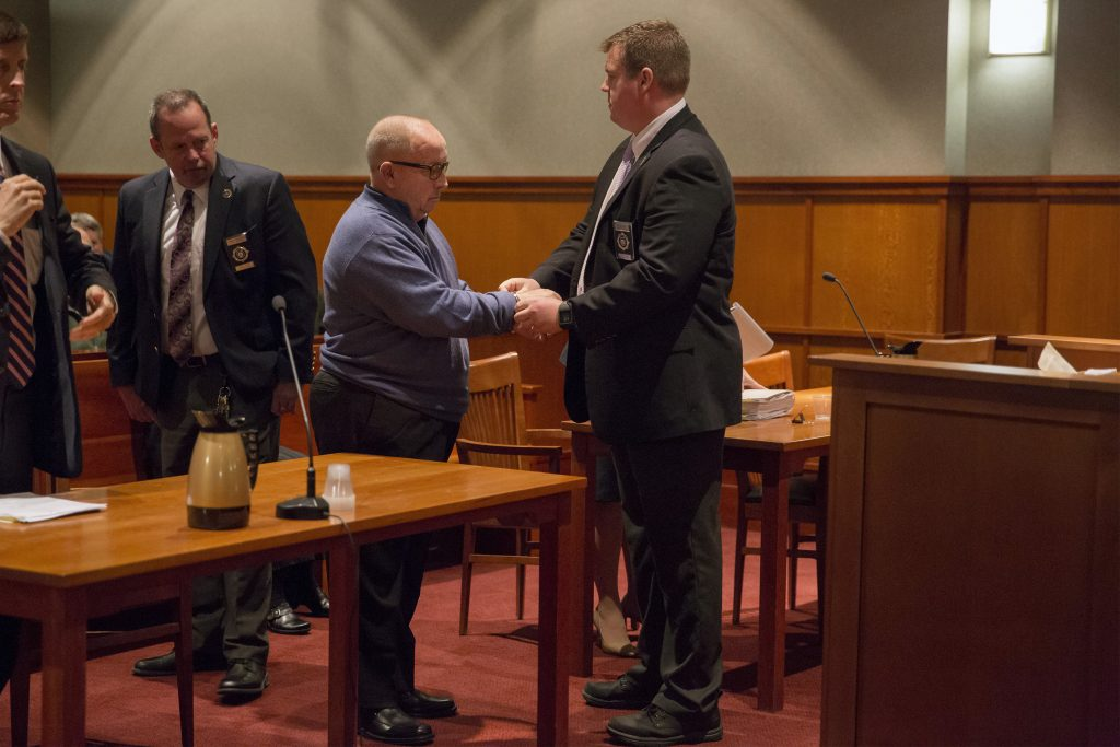 James Talbot, former priest and Cheverus High School teacher, is handcuffed by a bailiff after pleading guilty Monday to sexually assaulting a minor and being sentenced to serve three years in prison.