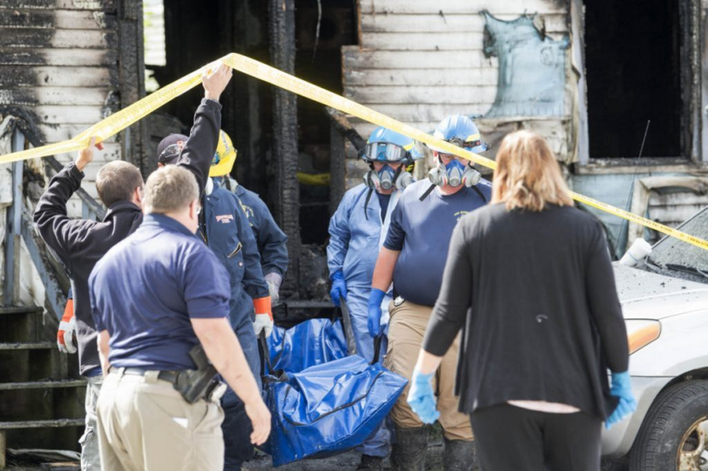 Investigators with the Office of State Fire Marshal remove the body of a man who died in a fire Friday on Milburn Street in Skowhegan.