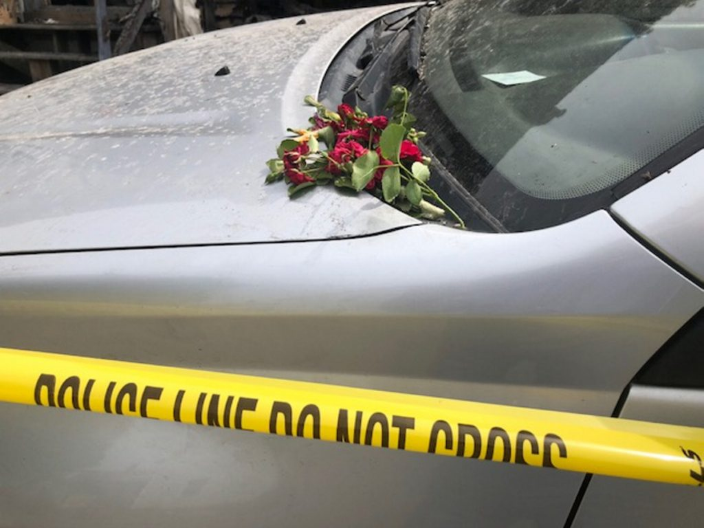 Someone placed a bunch of roses on a car inside the yellow police tape on Milburn Street in Skowhegan, where Douglas Barrett, 48, died in a fire Friday morning.