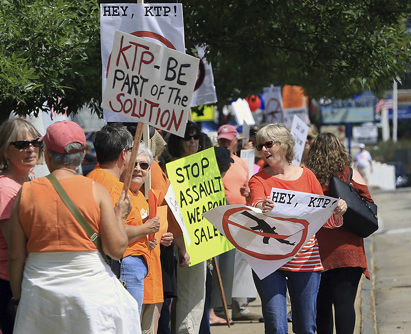 Protesters line up in front of Kittery Trading Post on Saturday to call for the business to stop selling assault-style rifles.