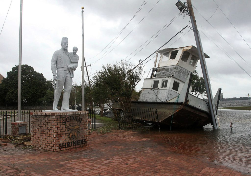 A tug boat sits next to a Shriner's Temple statue on East Front Street in New Bern, N.C., on Saturday. The boat washed up from the Neuse River with storm surge and debris from Hurricane Florence.