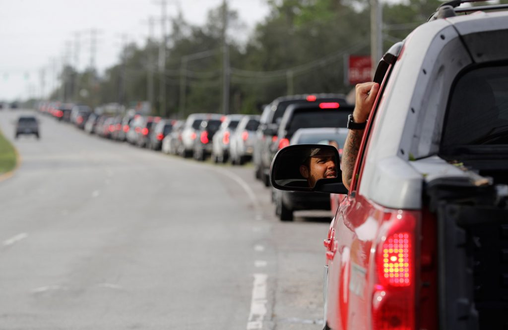 Motorists wait in a long line to buy gas at a station near Wilmington, N.C., on Monday. Floodwaters from Hurricane Florence cut off areas around Wilmington, forcing people to stand in long lines for fuel, food and other supplies.