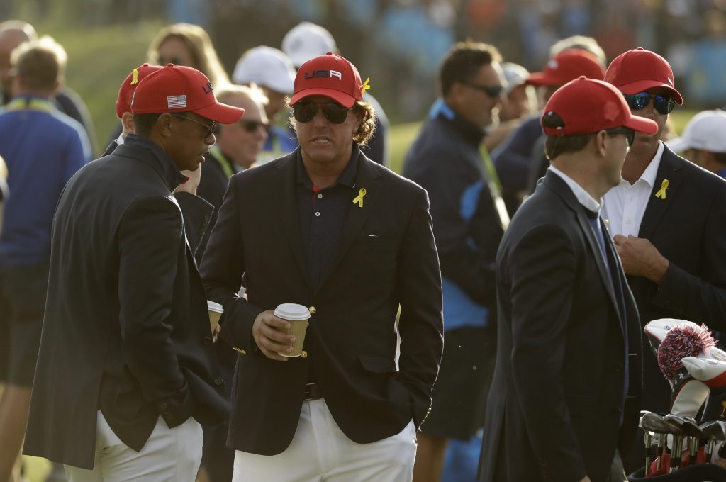 Tiger Woods, left, and Phil Mickelson, center, of the U.S. wait for the closing ceremony after another dismal showing at the Ryder Cup, which ended Sunday in a 171/2-101/2 victory for Europe.