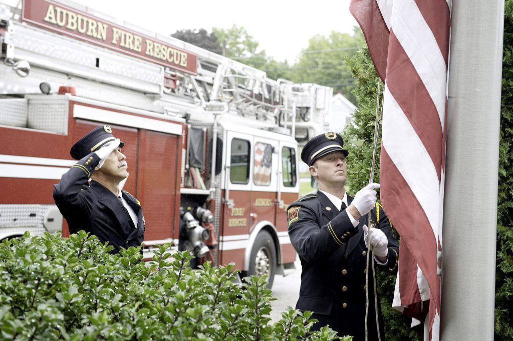 Auburn fire Capt. Chip Keene, left, and firefighter Ryan Demers raise the American flag during the 9/11 Memorial Ceremony at Central Station on Tuesday.
