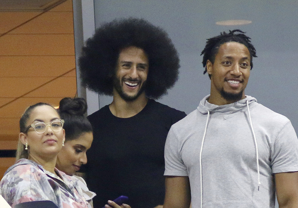 Colin Kaepernick, center, attends the third round of the U.S. Open in New York on Friday.