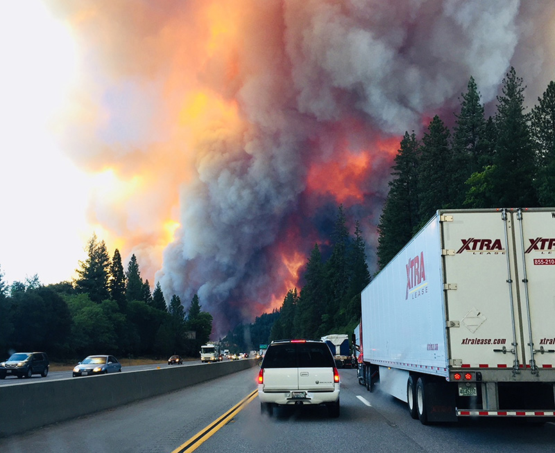 A fire rages as motorists travel on Interstate 5 near Lake Shasta, Calif. on Wednesday.