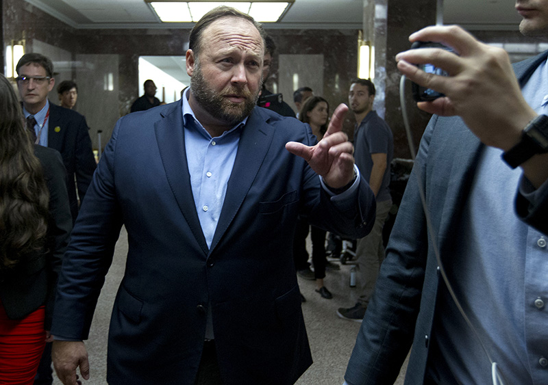Alex Jones, the right-wing conspiracy theorist, walks the corridors of Capitol Hill after listening to Facebook COO Sheryl Sandberg and Twitter CEO Jack Dorsey testify before the Senate Intelligence Committee .