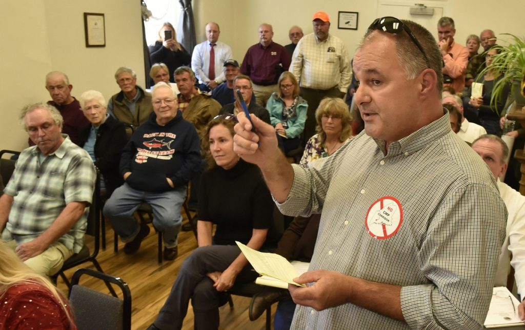 Wearing a sticker protesting the CMP New England Clean Energy Corridor project, Tom Michaud and others express opposition to the project during a Somerset County commissioners meeting in Skowhegan on Wednesday.