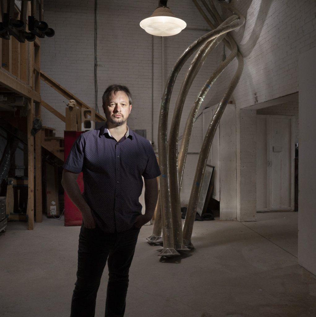 "Aaron Stephan poses with the curved poles of his sculpture  ""Luminous Arbor"" in his Portland studio Wednesday."