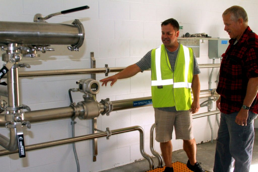 Mark Dubois, a Poland Spring hydrogeologist and the company's natural resource manager, points out a flow meter Thursday to Rumford Water Superintendent Brian Gagnon. This is one of two bore hole buildings from the Ellis spring site that will deliver water through more than 3 miles of pipeline to the loading station. Production will begin in 2019.