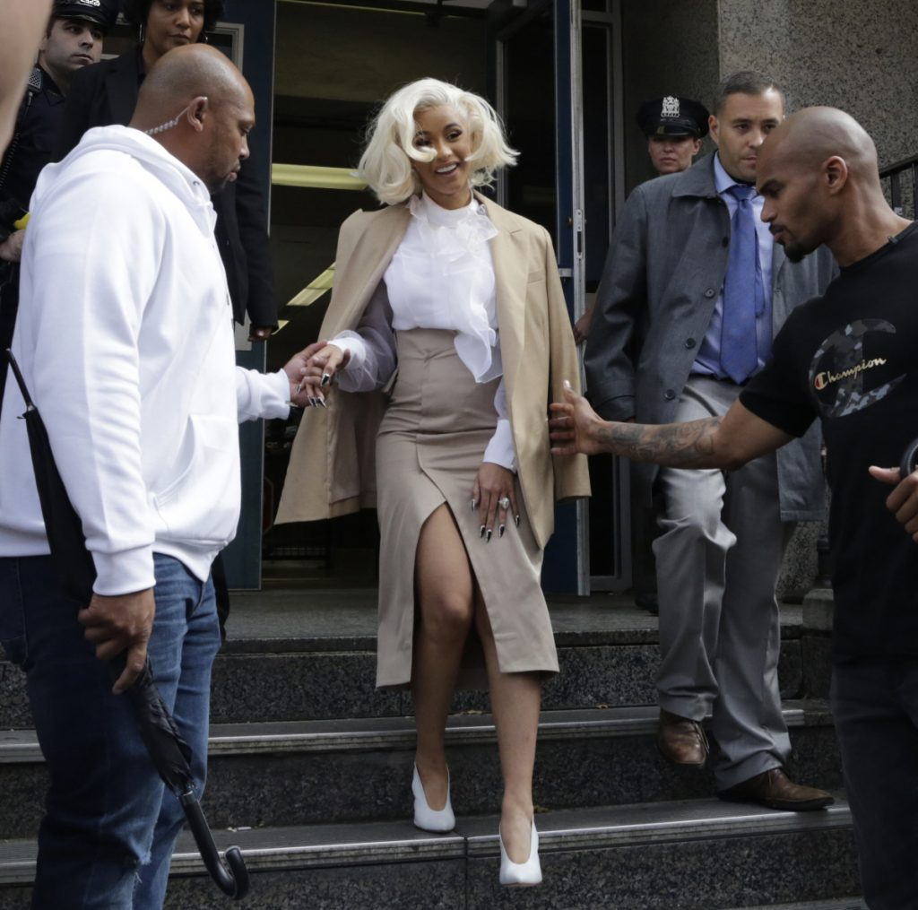 Rapper Cardi B is assisted by security guards as she leaves a police precinct Monday in Queens.